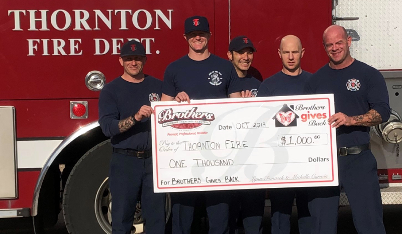 Brothers gives back to the Thornton fire department featured image of the fire depot holding a giant novelty check