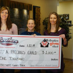Brothers Plumbing holds large check for A Precious Child campaign during January gives back presentation.