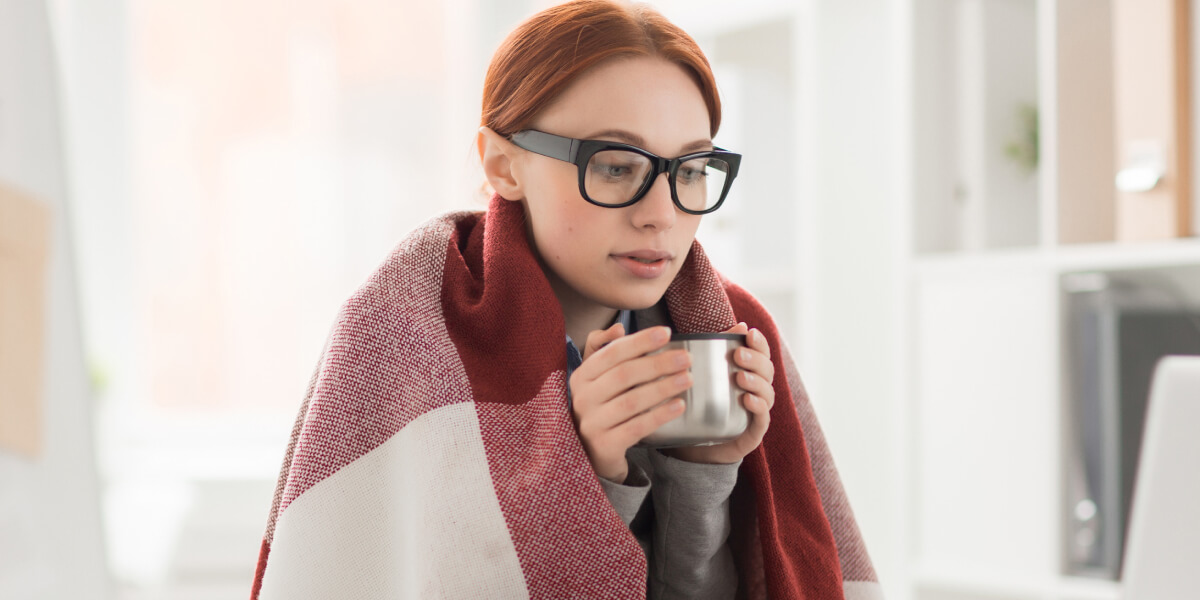 cold weather recommendations featured image featuring woman huddled by computer when it's cold